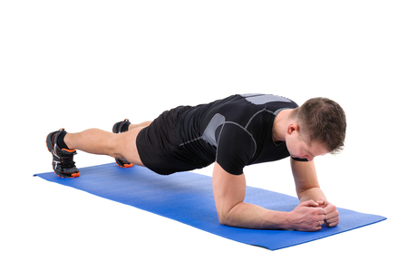 leaning on elbows: Young man shows Elbow Plank Workout, isolated on white, front view Stock Photo