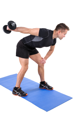 tricep: Young man shows finishing position of Standing Tricep Dumbbell Kickback workout, isolated on white Stock Photo