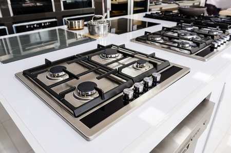 Rows of gas stoves with stainless tray selling in appliance retail store Stock Photo