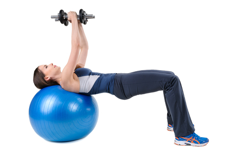 human chest: Young woman shows finishing position of Fitball Dumbbell Chest Flys Workout, isolated on white