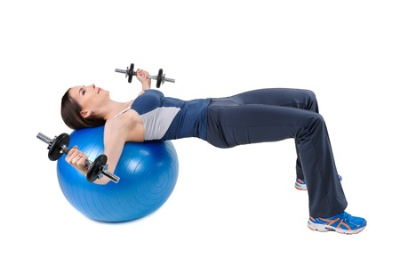 pectoral: Young woman shows starting position of Fitball Dumbbell Chest Flys Workout, isolated on white