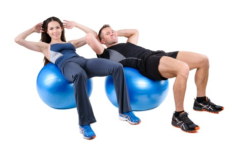 starting position: Young couple shows starting position of Abdominal Fitball Workout, isolated on white