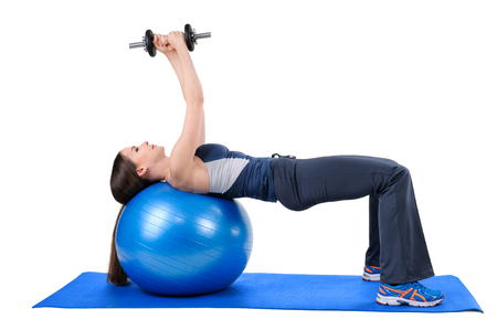 pectoral: Young woman shows finishing position of Fitness Ball Dumbbell Pullover Workout, isolated on white
