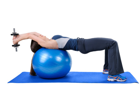 pullover: Young woman shows starting position of Fitness Ball Dumbbell Pullover Workout, isolated on white Stock Photo
