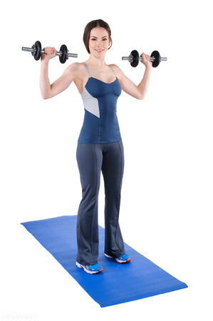 deltoid: young woman fitness instructor shows starting position of standing dumbbell shoulder press, isolated on white