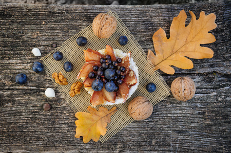 fruits in a basket: Romantic autumn still life with basket cake, walnuts, blackthorn berries and leaves, top view