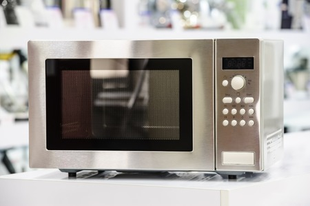 microondas: horno de microondas solo en estante de una tienda al por menor, el fondo desenfocado Foto de archivo