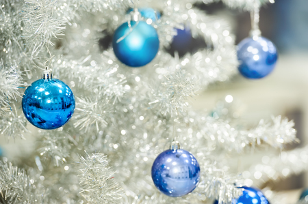 fir tree: Blue baubles hanging on silver artificial christmas tree, good as background Stock Photo