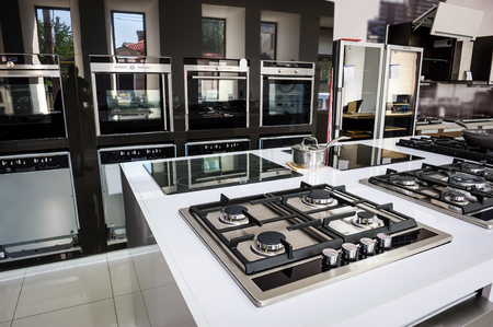 retail store: Rows of gas stoves with stainless tray selling in appliance retail store Stock Photo