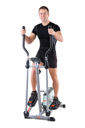 indoor background: young cute sporty woman doing exercises with elliptical trainer, on white background Stock Photo