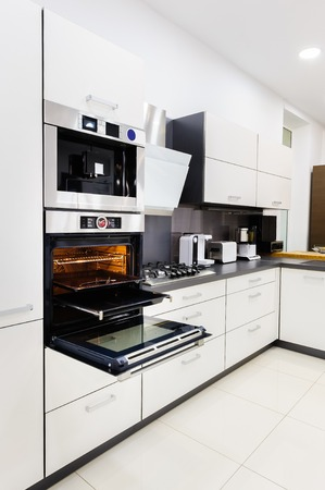 kitchen cabinet: Modern luxury hi-tek black and white kitchen, clean interior design, focu at oven with door open