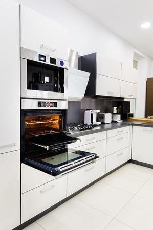 kitchen cupboard: Modern luxury hi-tek black and white kitchen, clean interior design, focu at oven with door open