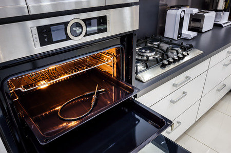 Moderne Luxus-hallo-tek schwarz und weiß Küche, saubere Innenarchitektur, focu bei Ofen bei geöffneter Tür Standard-Bild