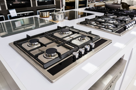 stoves: Rows of gas stoves with stainless tray selling in appliance retail store Stock Photo