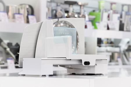 slicer: single white plastic electric food slicer at retail store shelf, defocused background Stock Photo