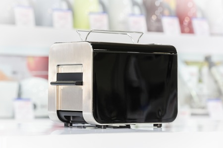 single shelf: Single brand new shiny black stainless steel and plastic toaster at retail store shelf, defocused background