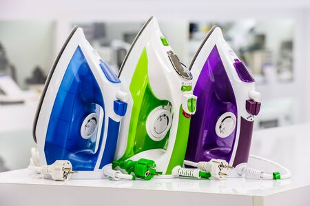 store shelf: three colored electric irons at retail store shelf, defocused background