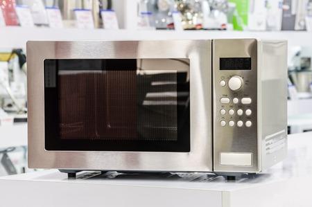 microondas: solo horno microondas met�lico de plata en estante de una tienda al por menor, el fondo desenfocado