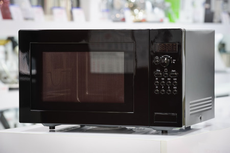 microwave oven: single black microwave oven at retail store shelf, defocused background