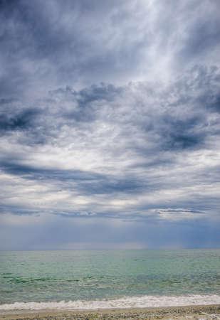 dark skies: rainstorm, heavy overcast raiclouds over the sea