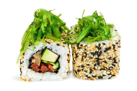 algas marinas: Uramaki de sushi maki, dos rollos aislado en blanco. Queso Philadelphia, anguila, pepino, tomates secos, aguacate y sésamo. Chuka algas en la parte superior.