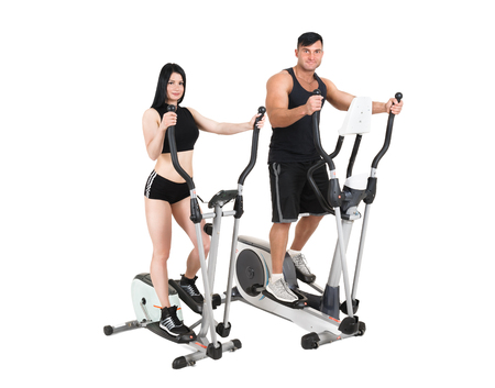 young pair of woman and man doing exercises with elliptical cross trainer together, isolated on white background