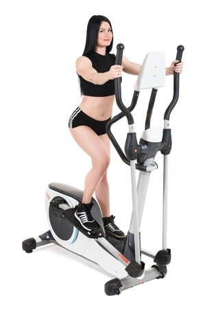 crosstrainer: young woman doing exercises with elliptical cross trainer, isolated on white background