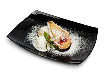 fruit plate: Baked Pear with Ice Cream Dessert, served on black square plate, isolated on white background