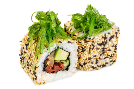 seaweed: Uramaki maki sushi, two rolls isolated on white. Philadelphia cheese, eel, cucumber, dried tomatoes, avocado and sesame. Chuka seaweed on top. Stock Photo