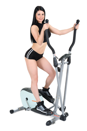 eliptica: young woman doing exercises with elliptical cross trainer, isolated on white background