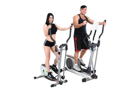 eliptica: joven pareja de la mujer y el hombre haciendo ejercicios con máquinas elípticas juntos, aislados sobre fondo blanco