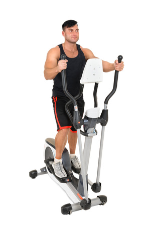 young handsome man doing exercises with elliptical trainer, isolated on white background