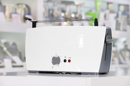 store shelf: Single brand new white plastic shiny toaster at retail store shelf, defocused background