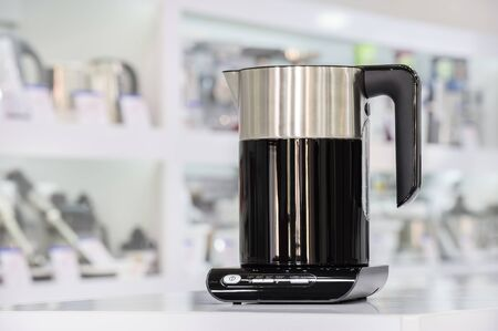 store shelf: Single brand new premium electric kettle at retail store shelf, defocused background