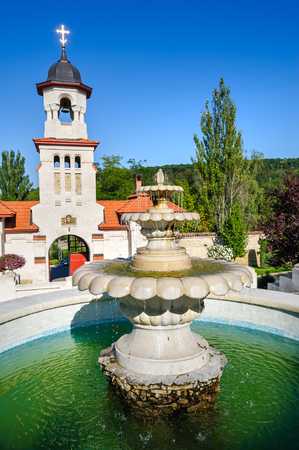 Fountain and entrance gates with bell tower, at Curchi Orthodox Christian Monastery, Moldova Stock Photo