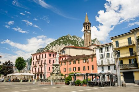 mario: Lecco, Italy - August 17th, 2016: Central streets of Lecco town, with cafe and bell tower. Monument of Mario Cermenati at foreground