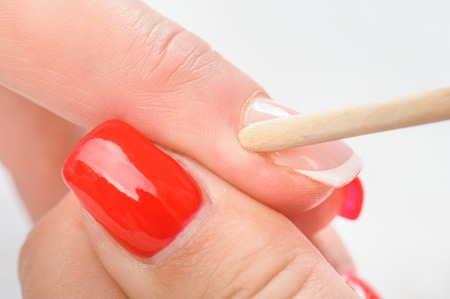 Nail salon, hands beauty treatment, cuticles care with bamboo wood cuticle pusher Stock Photo