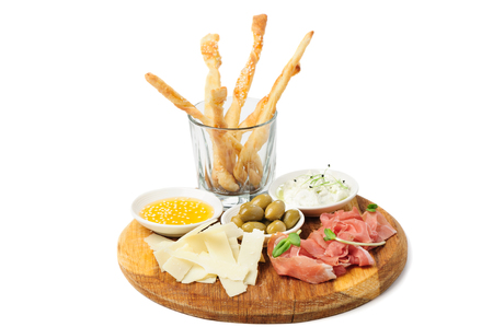 assortment: Assorted cheeses, wallnuts, prosciutto, green olives and other snacks served at wooden board