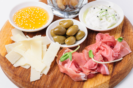 assorted: Assorted cheeses, wallnuts, prosciutto, green olives and other snacks served at wooden board