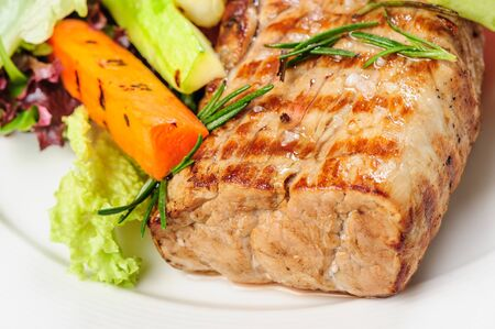 Grilled pork meat and vegetables on white plate with mustard sauce