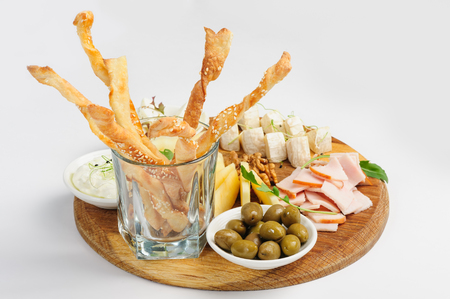 assortment: Assorted cheeses, wallnuts, prosciutto, green olives and other beer snacks served at wooden board, natural white background
