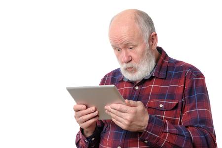 persona mayor: Senior hombre asombrado con algo en la pantalla de la computadora tablet, aislado en blanco Foto de archivo