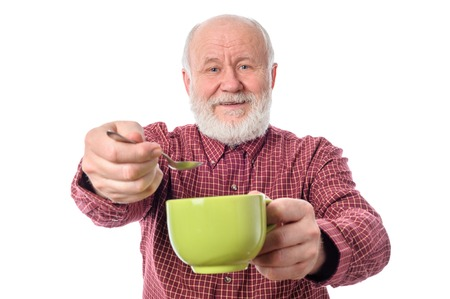 cheerfull: Cheerfull senior man with green cup and teaspoon, isolated on white