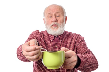 Cheerfull senior man with green cup and teaspoon, isolated on white