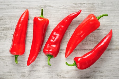 multiple objects: Sweet red Kapia peppers on a white wood background