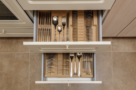 Opened kitchen drawer with silverware