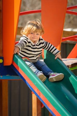 cute little toddler girl sliding down the childrens slide 免版税图像