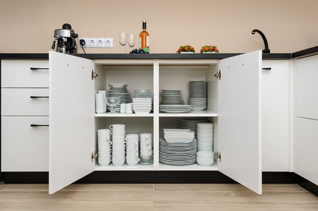 Dishware storage cabinet with plates and cups inside Stockfoto