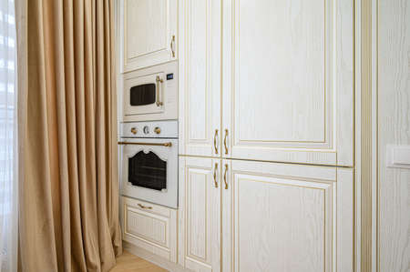 Electric and microwave ovens at beige kitchen interior Banco de Imagens