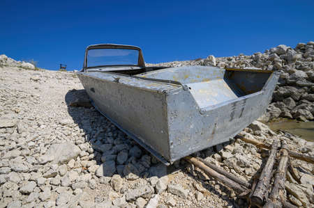 Empty old metal fishing motor boat at shore